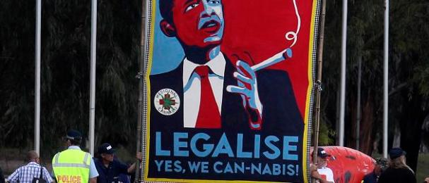Protesters hold giant sign to legalize marijuana before U.S. President Barack Obama arrives to participate in an official arrival ceremony at Parliment House in Canberra